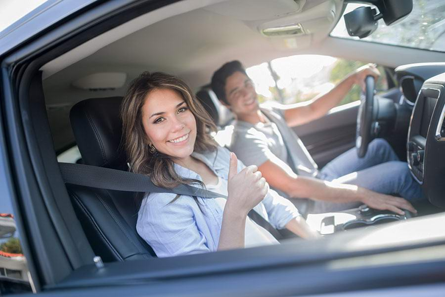 photo of two people buying a car smiling and giving a thumbs up