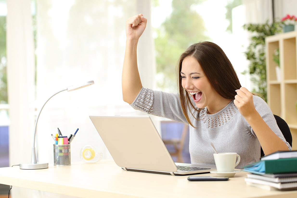 woman looking at her laptop and and smiling