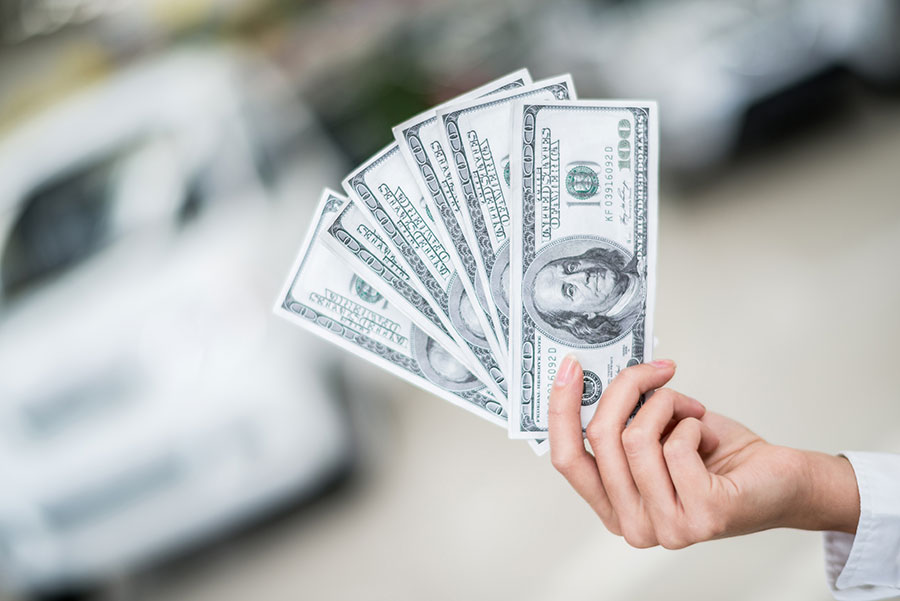 photo of a hand holding up 3 100dollar bills