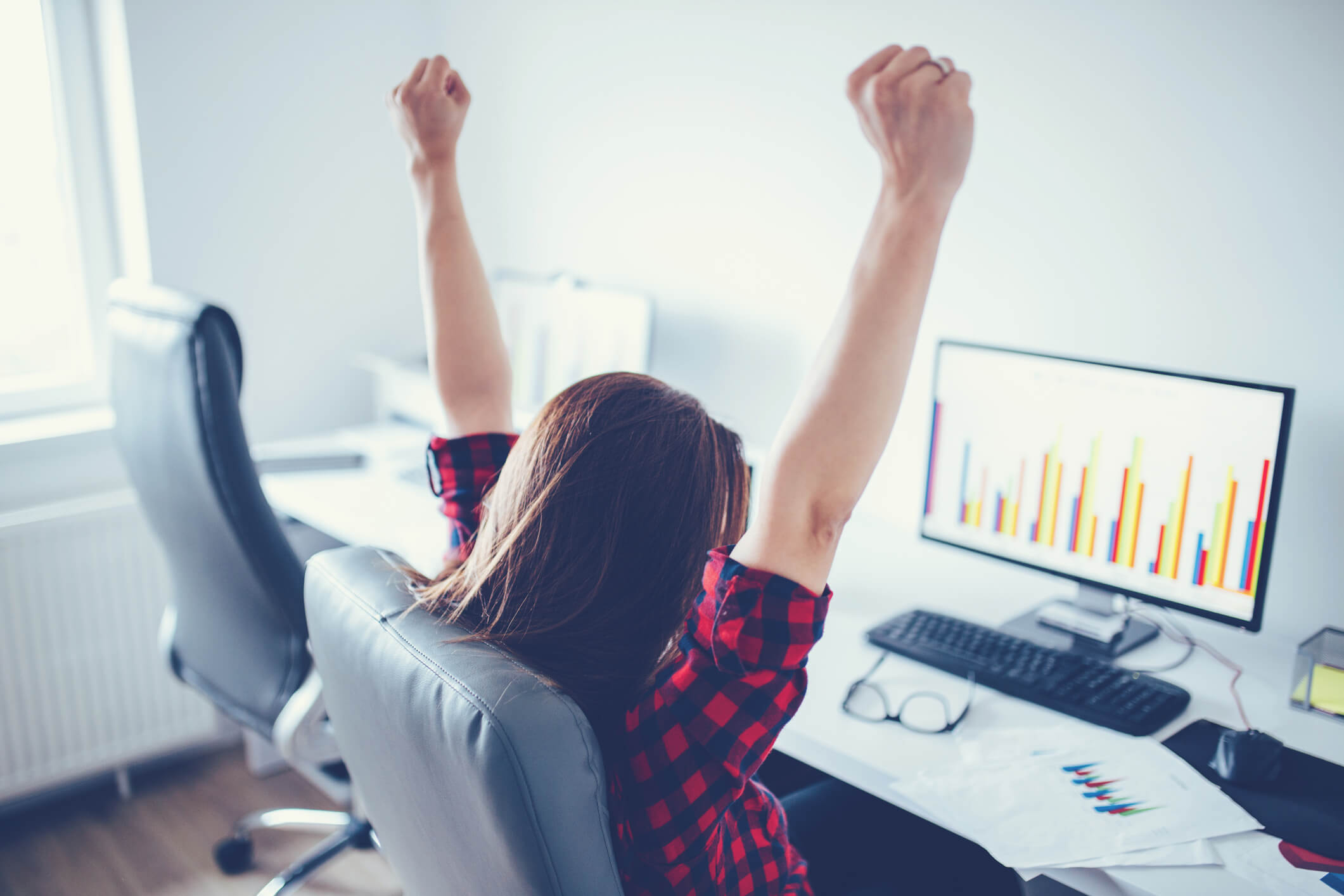 This is a photo of a woman cheering behind a computer wearing a plaid shirt, celebrating thee benefits of a title loan