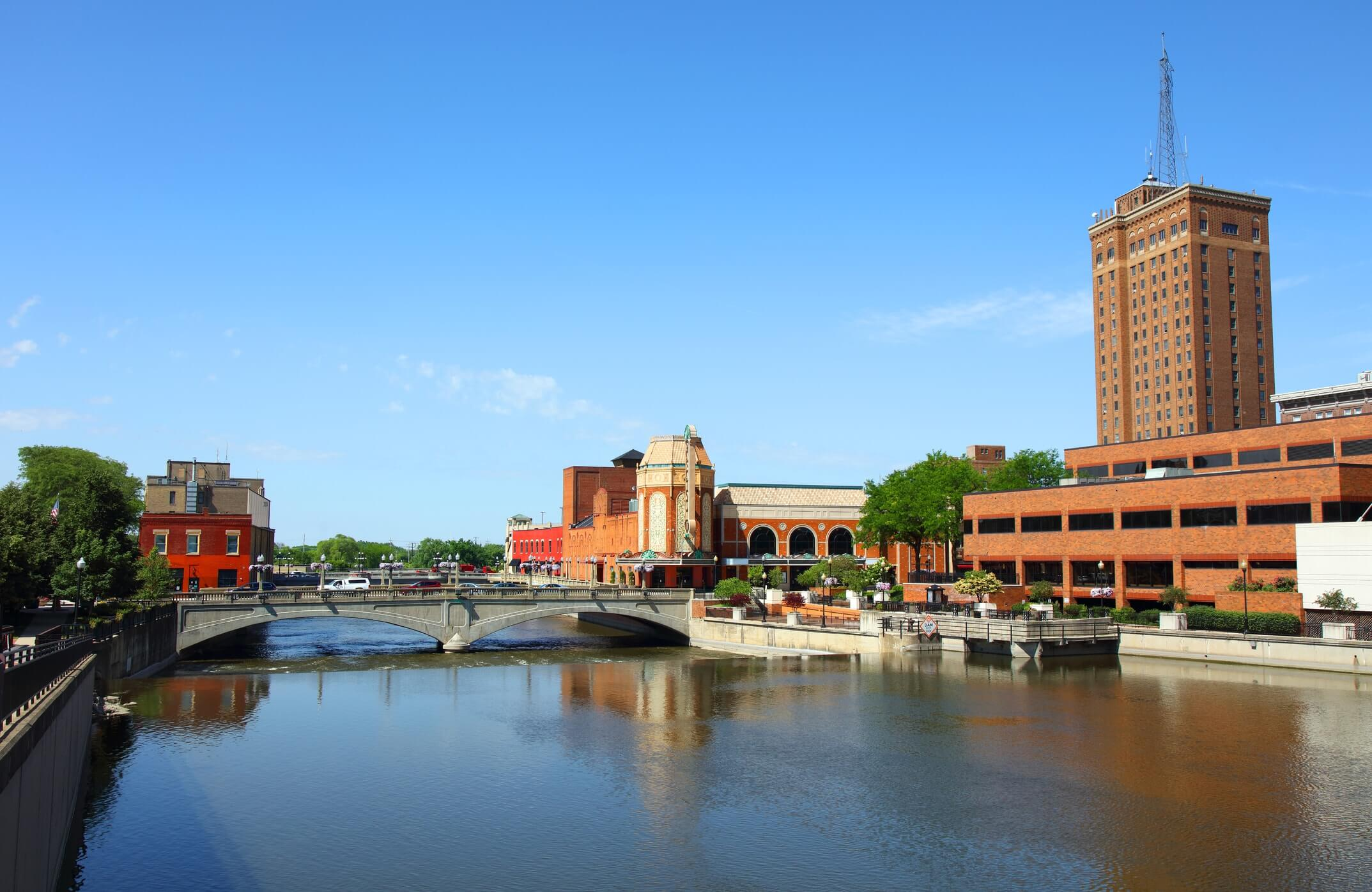 This is a photo of a river and a building in downtown Aurora Illinois