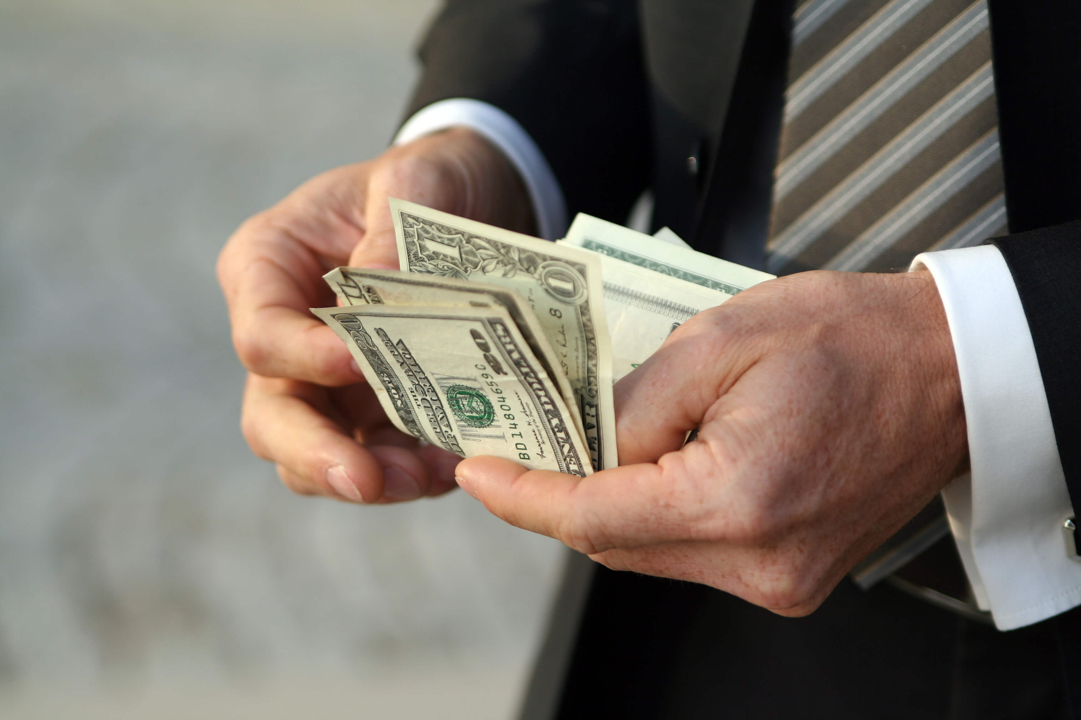 This is a photo of a man in a suit counting his cash, which represents people avoiding overpaying for title loans