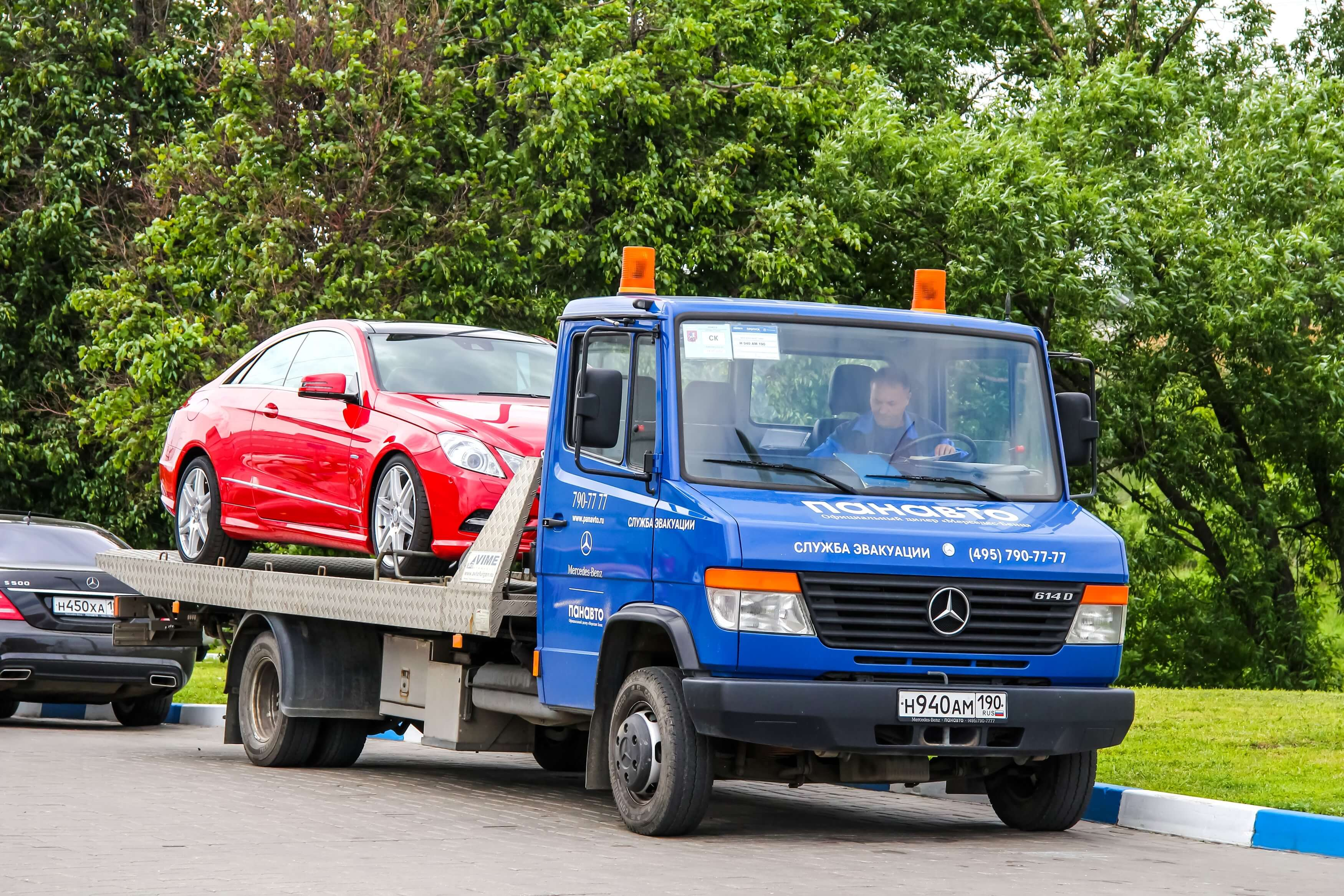 photo of a red mercedes in the bed of a tow truck