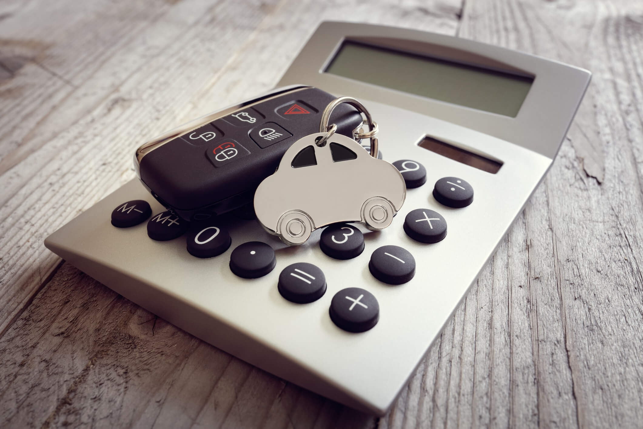 photo of car keys on top of a calculator