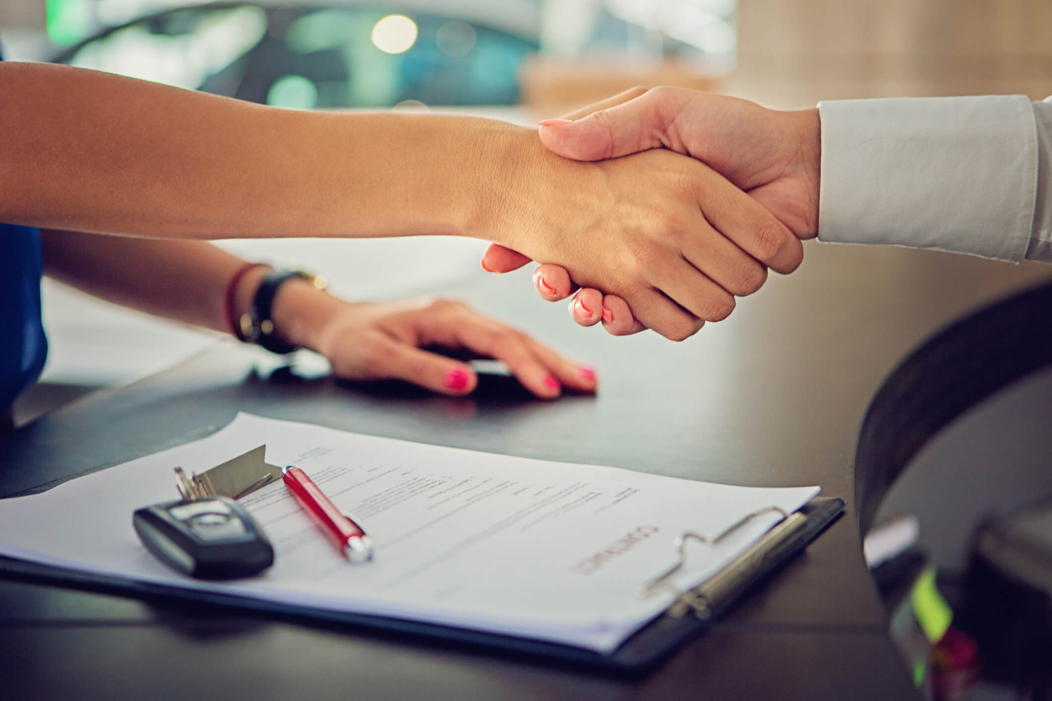 This is a photo of two peeople shaking hands, one being a woman, after completing a vehicle purchase. This represents selling a car with title loans debt