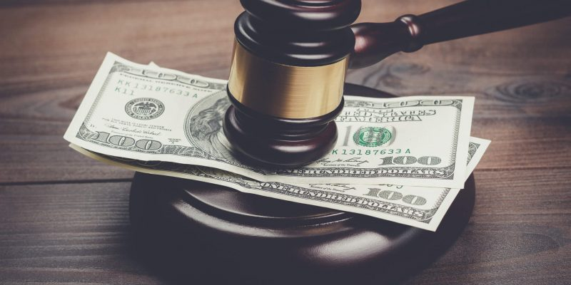 This is a photo of a court gavel slamming on money, to represent title loan buyout from titleloansonline.com