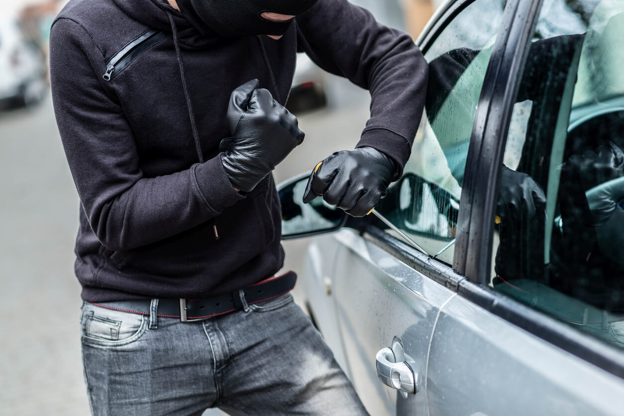 this is a photo of a criminal trying to break into a car
