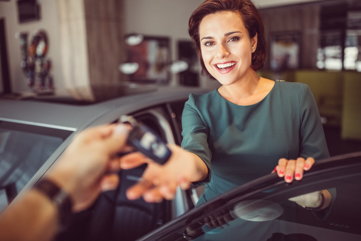 this is a photo of a woman getting car keys and smiling
