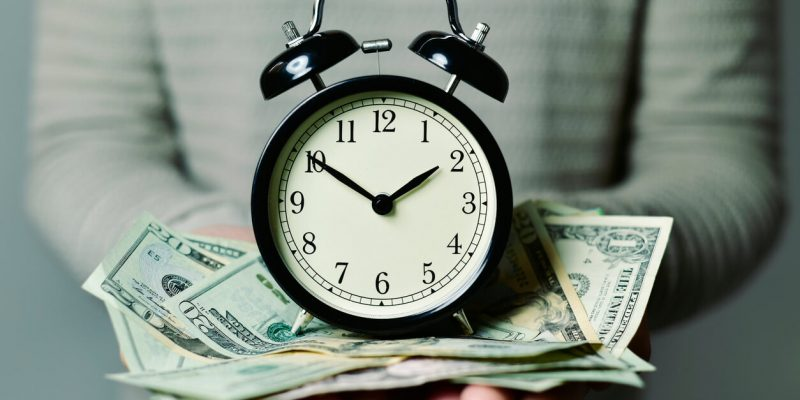 woman holding a clock with $20 bills in between the clock and her hands