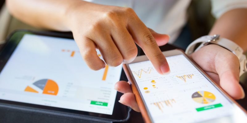 woman using a finance app on her phone and her tablet