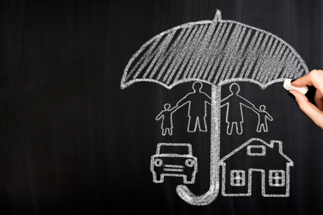 Chalkboard with a drawing of a family, car, and house all under a big umbrella