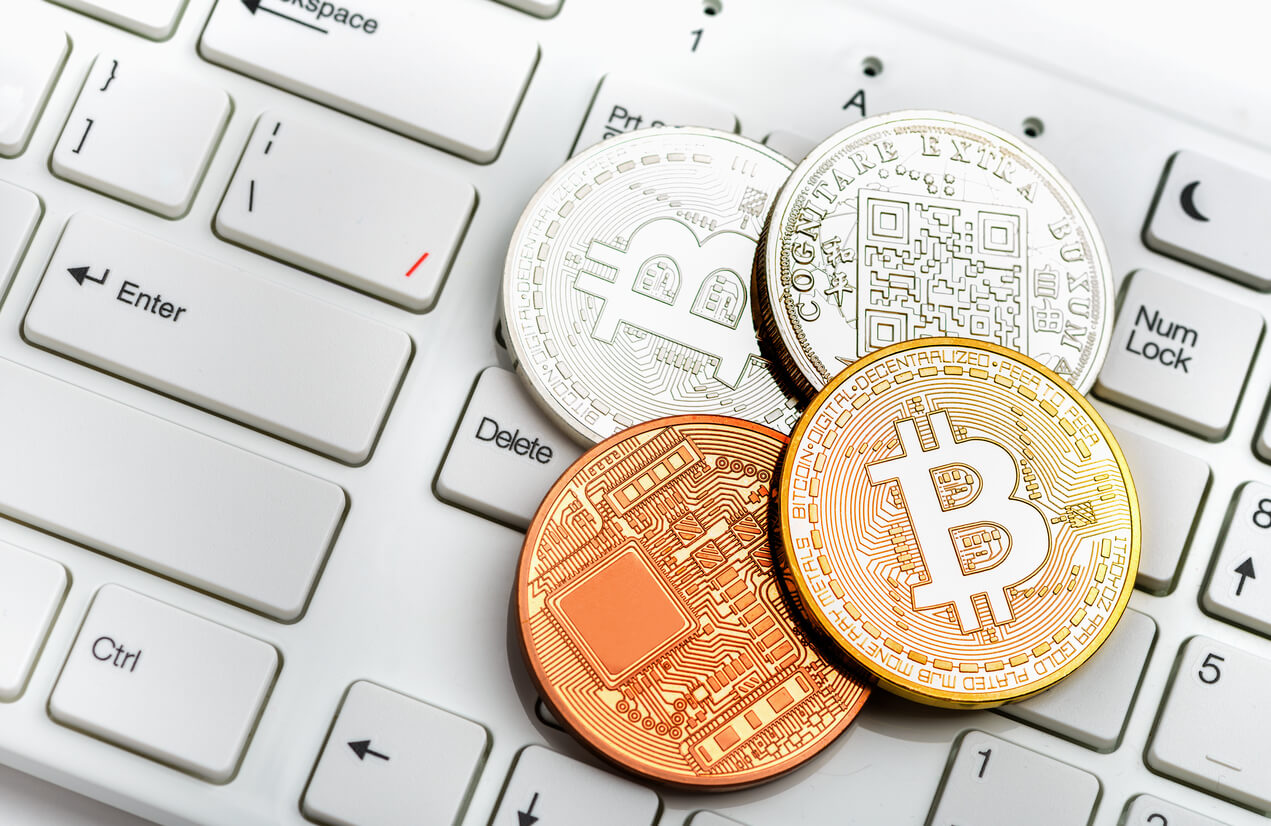bitcoin physical coins on top of a white keyboard