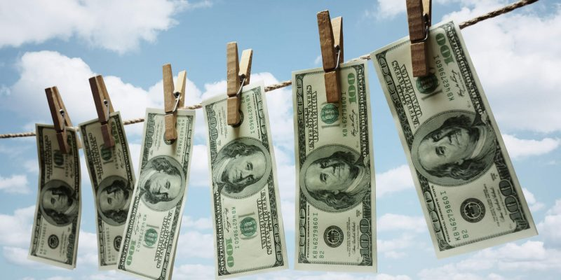 6 hundred dollar bills hung up on a clothesline to dry off
