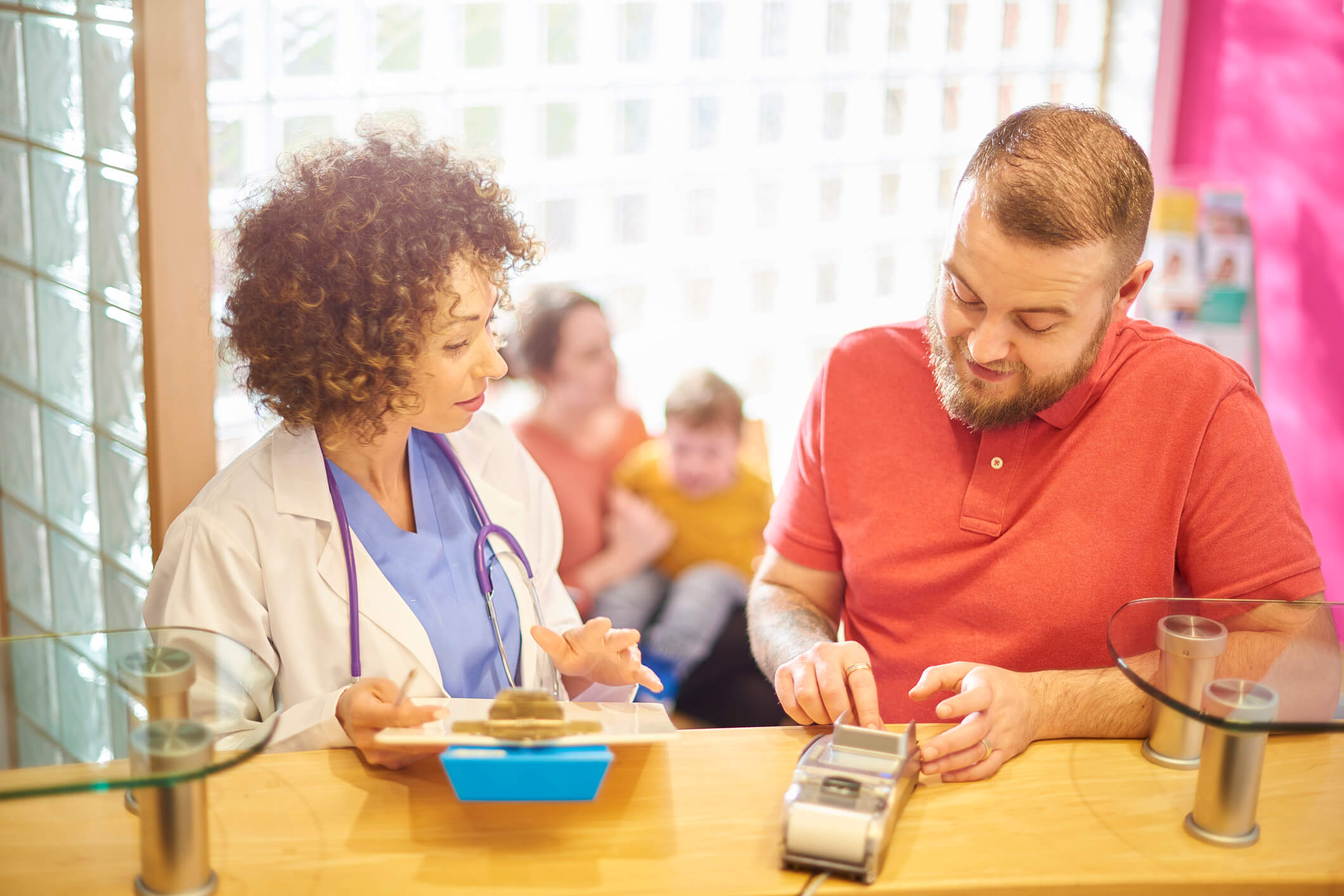 man talking to a doctor while checking out and paying his bill